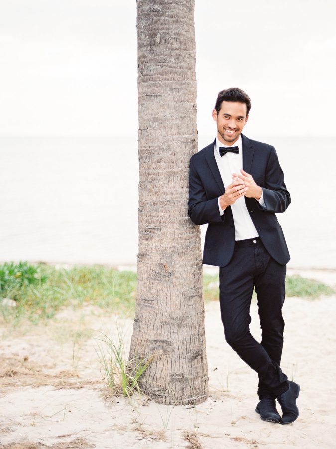 groom wearing black suit and bow tie